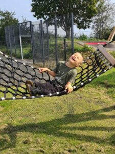 Cameron playing on swing