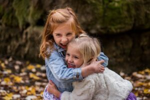Friends hugging outside with big smiles on their faces