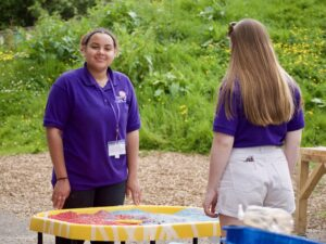 Playworker standing next to a child at a playtray